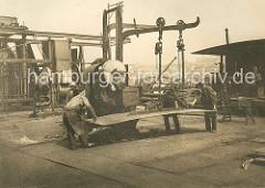 Eine Eisenplatte wird von den Werftarbeitern unter die Dampfschere gelegt. Schiffswerft und Maschinenfabrik Heinrich Brandenburg auf Hamburg Steinwerder.