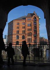 Hamburg Touristen stehen unter dem Speicher- gebäude H und sehen über das KLeine Fleet zur Brücke am Kannengiesserort. Dahinter die Stirnseite vom Lagerblock P mit seinen Ladeluken und den Winden, die mit einem Kupferdach geschützt sind.