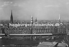 Blick über den Sandtorhafen und dem Sandtorkai zur Hamburger Speicherstadt mit ihren Giebeln und Türmen der Backsteinarchitektur. Schiffe liegen am Kai und werden entladen und die Ladung in den Lagerschuppen am Kaispeicher verstaut.