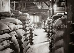 Ein Quartiersmann steht an der Waage auf dem Speicherboden im Hamburger Freihafen. Der Rohkaffee ist in Jutesäcken vernäht, die auf dem Lagerboden des Speichers gestapelt sind.