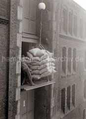 Eine Hieve mit Kaffeesäcken wird auf dem Lagerboden von den Lagerarbeitern in Empfang genommen. Sie ziehen die Ladung in die Türöffnung, um die Säcke dann ins Lager zu transportieren.