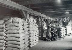 Säcke mit Kaffeebohnen sind auf einem Speicherboden im Kaispeicher A / Kaiserspeicher gelagert. Lagerarbeiter wiegen Kaffeesäcke mit einer transportablen Waage - die nicht genutzten Gewichte stehen auf einem kleinen Wagen mit Rädern.