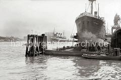 Der Frachter FLOTTBEK liegt eingedockt im Trockendock. Werftarbeiter stehen auf Leitern und Gerüsten und arbeiten am Schiffsrumpf.  Im Hintergrund die Einfahrt zum Grasbrookhafen.