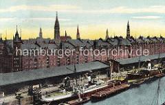 Zwei Dampfschiffe liegen am Sandtorkai des Sandtorhafens. Auf der Landseite werden die Schiffe über Kräne be- und entladen und auf der Wasserseite Schuten und Lastkähne liegen.