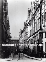 Blick in den neuen Wandrahm kurz bevor die Abrissarbeiten für den Bau der Hamburger Speicherstadt beginnen. Die Häuser haben prächtig dekorierte Barock - Fassaden, ein Pferdewagen transportiert Waren über das Kopfsteinpflaster.