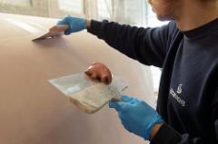 Ausfleckarbeiten am Schiffsrumpf vom Daysailer auf der Lütje Werft- restliche kleine Unebenheiten werden mit Epoxidspachtelmasse ausgefüllt,