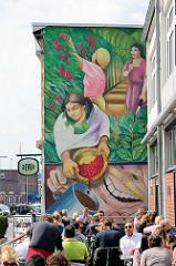 Wandbild an einer Hausfassade in Hamburg Altona - Kaffeepflückerinnen bei der Arbeit - lachender Kaffeetrinker; Restaurant mit Aussengastronomie.