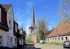 Wohnhäuser; Kirchturm und Kirchenschiff der Immanuelkirche in Wedel.