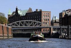 eine Barkasse der Hamburger Hafenrundfahrt fährt mit Hamburg Touristen im Zollkanal, der ehemalige Zollgrenze am Freihafen bei der Hamburger Speicherstadt. Die Kibbelstegbrücke führt über den Kanal zur Hamburger Hafencity.  In der Bildmitte das S