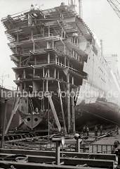 An einem Passagierschiff der HAPAG Reederei wird im Schwimmdock der Werft Bohm & Voss gearbeitet - u.a. wurde 1933/34 der Turbinen-Schnelldampfer  Deutschland (IV) von 183m auf 197m auf der Hamburger Werft verlängert.