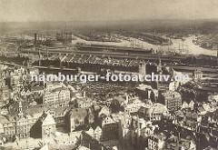 Luftaufnahme von Hamburg - im Binnenhafen in der Bildmitte liegen die Schiffe dicht gedrängt, dahinter die hohe Architektur der Speicher in der Hamburger Speicherstadt. Lang gestreckt liegen die Schuppen an den Kais vom Sandtorhafen und Grasbrook