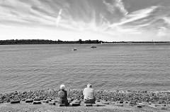 Elbufer der Unterelbe bei Wedel - ein älteres Paar sitzt auf der Uferbefestigung und blickt auf die Elbe - Schwarz Weiss Aufnahme.