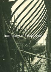 Schiffswerft und Maschinenfabrik Blohm & Voss im Hamburger Hafen - ein Doppelschraubendampfer liegt auf der Helling. Der Schiffsboden ist gelegt, Hintersteven und Spanten sind zu erkennen.