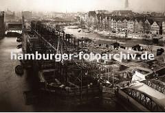 der Bau der neuen Hamburger Speicherstadt hat begonnen - die Fleete sind ausgehoben und werden mit neu errichteten Brücken überspannt, Schuten transportieren das Baumaterial. Im Vordergrund wird der Speicherblock G gebaut.
