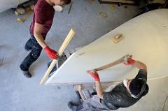 Der Bootsrumpf des Daysailers ist mit einer Schicht Spritzspachtel versehen und wird erneut geschliffen.