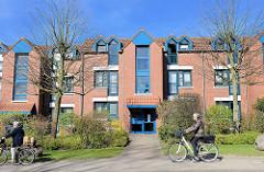 Moderne Wohnblocks mit Dachwohnungen - blau abgesetzte Fensterelemente - RadfahrerInnen in der Austrasse von Wedel.