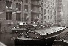 Lastkähne im Wandrahms Fleet der Speicherstadt Hamburg. Die Ladung eines der Binnenschiffe wird gelöscht - eine Hieve Säcke wir über eine Winde auf einen der Lagerböden des Speicherblocks S gebracht.