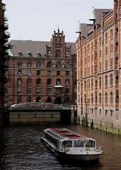 ein Schiff der Hafenrundfahrt kommt vom Kleinen Fleet und fährt im Wandrahmsfleet - an Bord Hamburg Touristen, die sich die Sehenswürdigkeiten der Hansestadt Hamburg ansehen. Die Barkassen sind so flach gebaut, damit sie auch bei Flut die vielen