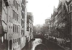 Bilder aus dem alten Hamburg - Blick auf die Wohngebäude und Geschäftshäuser in der HOLLÄNDISCHEN REIHE. Handkarren stehen auf dem Kopfsteinpflaster der Strasse. Eine Schute liegt an der Mauer des Fleets.