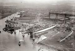 Luftaufnahme der Deutschen Werft in Hamburg Finkenwerder - ein Schiffsneubau liegt auf der Helge; das umstehende Publikum wartet auf den Stapellauf, wie auch die kleinen Boote, die im Vordergrund auf dem Wasser zu erkennen sind.