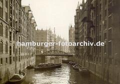 Schuten im Fleet in der Hamburger Speicherstadt - die Kähne sind mit Säcken beladen und an den Ringen, die in der Speichermauern eingelassen sind fest gemacht. Eine über dem Wasser hängende Lampe soll die Arbeiten in der Dunkelheit erleichtern.