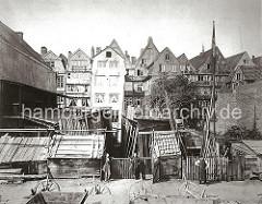 Blick auf das Lager und die Werkstatt einer Stellmacherei am Sandtorkai; unterschiedliche Hölzer werden in Schuppen und im Freien gelagert. Im Vordergrund sind unterschiedliche Fuhrwerke aus Holz zu erkennen.