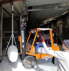 Vorbereitungsarbeiten für die Lackierung vom Edelstahlkiel - mit einem Gabelstabler wird der schwere Kiel angehoben.