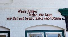 Inschrift am historischen Gebäude, Marktplatz von Wedel: Gott schütze dieses alte Haus vor Not und Feuer Krieg und Steuer.