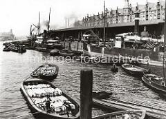 Blick in den Sandtorhafen - Frachter liegen am Kai; Binnenschiffe und Schuten haben längsseits fest gemacht. Im Vordergrund bewegen zwei Ewerführer ihre mit Holzkisten beladenen Schuten mit dem Peekhaken / Bootshaken durch das Hafenbecken.