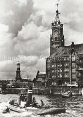 Elbseite des Kaiserspeichers - Uhrenturm; Schlepper und Barkasse auf der Elbe. Im Hintergrund die St. Michaeliskirche, dem Wahrzeichen Hamburgs.