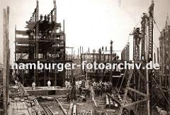 die Eisenträger des Speicherblock H werden hoch gezogen - Bauarbeiter balancieren auf dem Gerüst; einfach zusammen genagelte Holzleitern werden zum Besteigen der Hamburger Grossbaustelle benutzt.