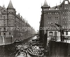 Schuten und Binnenschiffe im Kehrwiederfleet; im Hintergrund die Kehrwiederbrücke - rechts der Speicherblock J und links der Speicher A. Hinter dem Kran sind leere Handkarren geparkt. Die Schiffe haben Holzfässer und Säcke geladen; einer der