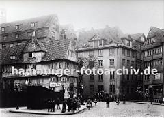 Strassenkreuzung im Bereich Pickhuben - die historischen Häuser stehen dicht gedrängt in dem zukünftigen Areal der Hamburger Speicherstadt. Ein Ladenschild links weist auf eine Barbier Stube hin sowie auf einen Klempner und Mechaniker.
