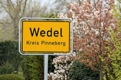 Ortsschild / Stadtschild Wedel, Kreis Pinneberg - im Hintergrund blühende Sträucher.