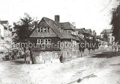 Fachwerk-Wohnhäuser in der Dienerreihe - die Gebäude wurden für die Ratsdiener errichtet; rechts im Hintergrund der Turm der ehemaligen St. Annen Kapelle. Links stehen leere Holzfuhrwerke am Strassenrand.