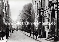 Blick in den alten Wandrahm kurz bevor die Abrissarbeiten für den Bau der Hamburger Speicherstadt beginnen. Die Häuser haben prächtig dekorierte Barock - Eingänge, Strassenlaternen sind an der Hausfassade angebracht oder stehen am Strassenrand.