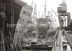 Schwimmdock der 1877 gegründeten Werft Blohm & Voss - Werftkräne stehen am Rand des Docks und transportieren Arbeitsmaterial zum Schiff. Im Vordergrund liegen ein Schwimmkran und eine Arbeitsschute.