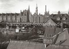 Blick über den Sandtorhafen zu den neogotischen Backsteinbauten der Hamburger Speicherstadt. Am Sandtorkai liegt ein Frachtschiff, dahinter die Hafenkräne vor dem Lagerschuppen 7.
