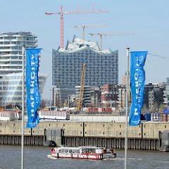 Flaggen der Hafencity Hamburg, eine Barkasse fährt am Chicagokai / Strandkai; Baukräne und Baustelle der Elbphilharmonie.