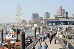 Promenade an der Elbe in Hamburg - Spaziergänger am Wasser; Schlepper liegen am Ufer. Im Hintergrund das Museumsschiff Rickmer Rickmers und die Skyline von Hamburg St. Pauli.
