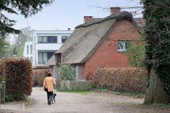 Reetgedecktes Wohnhaus in Wedel, dahinter ein Neubau.