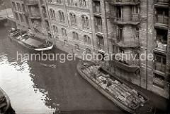 Ein Motorschiff und eine Schute liegen an der Mauer eines Lagerschuppens auf einem Fleet in der Hamburger Speicherstadt. Die Ladung der Schiffe wird über Winden gelöscht. Eine Hieve Säcke wird zum Lagerraum hochgezogen.