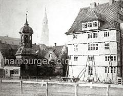 Turm der St. Annen Kapelle und im Hintergrund die St. Katharinenkirche - rechts ein mehrstöckiges Fachwerkhaus; die Scheiben sind teilweise zerbrochen und die unteren Fenster vernagelt. Die Aussenmauer des Gebäudes wird mit Balken abgestützt.
