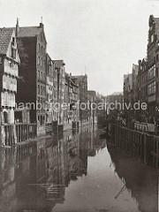 Blick auf den Holländischen Brook - Handkarren stehen entlang der gepflasterten Strasse, mit kleinen Kränen kann die Ladung der Schuten an Land gebracht werden. An den Lagergebäuden der Wasserseite des Fleets befinden sich Winden-