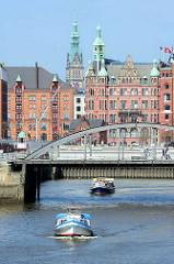 Barkassen der Hamburger Hafenrundfahrt fahren im Magdeburger Hafen - im Hintergrund das Speicherstadt- Rathaus, Sitz der HHLA und der Turm vom Hamburger Rathaus.