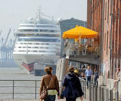 Uferpromenade an der Elbe in Hamburg Altona - Restaurant mit Sonnenschirmen am Wasser - Kreuzfahrtschiff am Altonaer Terminal.