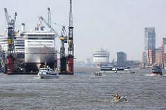 Hamburger Hafen - eingedockte Passagierschiffe; Fahrgastschiffe und Sportboote auf der Elbe; im Hintergrund liegt ein Passagierschiff am Kreuzfahrtterminal Altona.