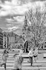 Frühling in der Hamburger Hafencity - blühender Kirschbaum, Architektur der Speicherstadt; laufende Kinder auf dem Dar es Salaam Platz.