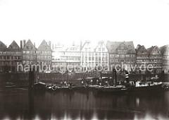 Vor den mehrstöckigen Wohngebäuden liegt ein Schlepper mit hohem Schornstein unter Dampf. Dahinter stehen die Ewerführer mit ihren Bootshaken auf ihren Schuten.