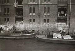 Warenumschlag in der Speicherstadt - die Ladung zweier Schuten wird gelöscht. Mit den Winden, die sich unter den Dächern der Speichergebäude befinden, werden die Säcke auf die Böden der Lagerräume gebracht.